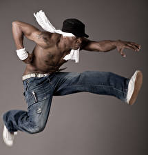 Bilder Mann Grauer Hintergrund Baseballkappe Jeans Sprung Tanz Hand Neger