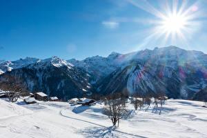 Papel de Parede Desktop Suíça Montanhas Invierno Edifício Alpes Neve Raios de luz Braunwald Naturaleza