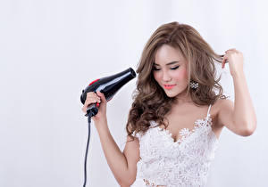 Image Asiatic Gray background Brown haired Hair Smile Hands Hair dryer Girls