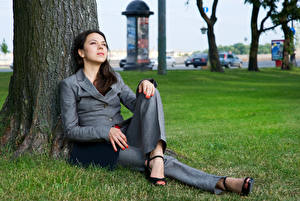 Fotos Brünette Sitzend Baumstamm Blick Anzug Mädchens