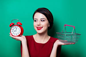 Wallpapers Clock Alarm clock Colored background Brunette girl Smile Wicker basket Hands Red lips Girls