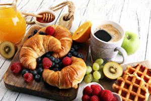Bilder Kaffee Croissant Honig Obst Himbeeren Heidelbeeren Weintraube Frühstück Schneidebrett Tasse