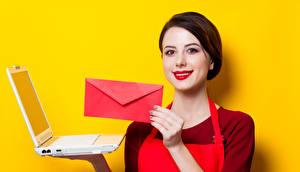 Fotos Farbigen hintergrund Braunhaarige Lächeln Rote Lippen Notebook Hand Brief Junge frau Mädchens