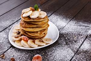Фото Блины Бананы Сахарная пудра Тарелка Доски Пища
