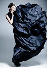Fotos Grauer Hintergrund Brünette Kleid Hand Mädchens