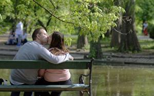 Pictures Men Lovers Bench Two Sitting Kisses Hug young woman