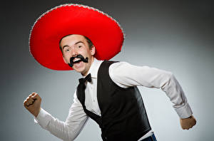 Photo Man Gray background Joyful Moustache Hat Hands Sombrero