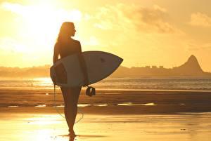 Bilder Morgendämmerung und Sonnenuntergang Wellenreiten Strände Silhouette Sport Mädchens