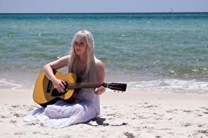 Fotos Meer Strände Blondine Kleid Sitzend Gitarre Mädchens