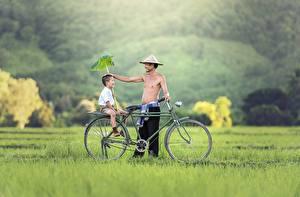 Hintergrundbilder Asiatische Mann Gras 2 Fahrräder Jungen Sitzt Lächeln