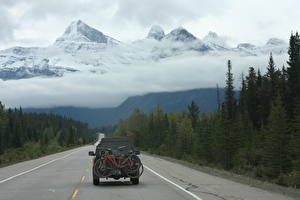 Wallpapers Canada Mountains Forests Roads Snow Clouds Bike Back view Rocky Mountains, Alberta Nature