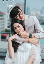 Wallpaper Men Lovers Asiatic Two Hugging Hat Glasses Smile Brunette girl Hands Guy young woman