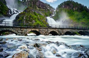Bilder Norwegen Lofoten Brücke Wasserfall Steine Felsen Laubmoose Natur