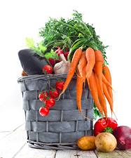 Fotos Gemüse Mohrrübe Kartoffel Tomaten Weißer hintergrund Weidenkorb das Essen