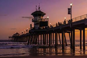 Fotos USA Brücken Schiffsanleger Abend Wasserwelle Ozean Kalifornien Bucht Straßenlaterne Huntington Beach Pier Natur