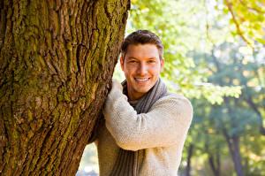 Fotos Mann Rinde Lächeln Blick Baumstamm Sweatshirt