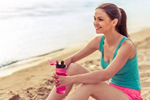 Fotos Fitness Braune Haare Sitzt Lächeln junge Frauen Sport