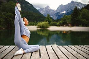 Fotos Fitness Gymnastik Körperliche Aktivität Lächeln Bein Dehnübung Bokeh Mädchens Sport