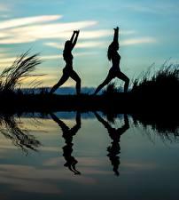 Bilder Morgendämmerung und Sonnenuntergang Spiegelung Spiegelbild Zwei Silhouette Joga Körperliche Aktivität Sport