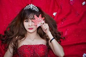 Bilder Asiaten Krone Braunhaarige Blatt Starren Roter Hintergrund Haar Frisur Mädchens