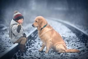 Fotos Hunde Golden Retriever Winter Eisenbahn Jungen Sitzend Mütze Jacke Marianna Smolina kind