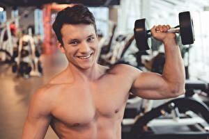 Fotos Mann Fitness Starren Lächeln Hand Hantel Muskeln Unscharfer Hintergrund Sport