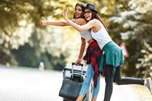 Fotos Tourist Zwei Der Hut Brille Lachen Hand Glücklicher Koffer junge Frauen