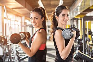 Hintergrundbilder Trainieren Zwei Starren Lächeln Hand Hanteln Bokeh sportliches Mädchens
