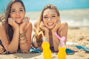 Fotos Strand Sand 2 Blick Lächeln Hand Braune Haare junge Frauen