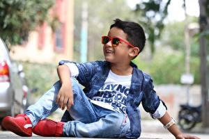 Bureaubladachtergronden Jongen Bril Glimlach Zitten Jeans Een jas kind