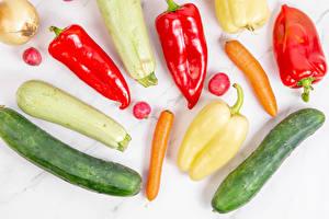 Bureaubladachtergronden Wortels Courgette Komkommers Paprika Radijs Uien Groente Witte achtergrond