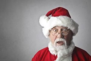 Fotos Neujahr Mann Grauer Hintergrund Weihnachtsmann Mütze Starren Brille Überraschtes
