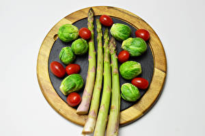 Photo Vegetables Tomatoes Gray background Cutting board Asparagus Brussels sprout