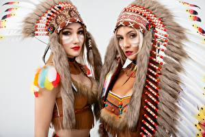 Desktop wallpapers Warbonnets Indians Beautiful Gray background Two Staring Vitaly Rychkov female