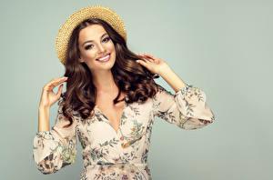 Fotos Grauer Hintergrund Braune Haare Der Hut Haar Lächeln Hand Starren Frisur Mädchens