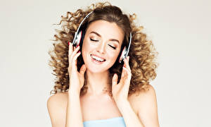 Photo Gray background Brown haired Headphones Hands Smile Lovely Girls