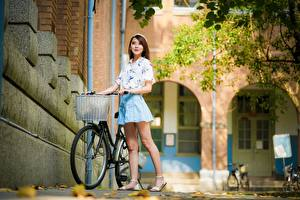 Pictures Asiatic Blurred background Posing Bike Brown haired Legs young woman
