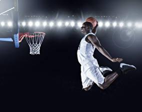 Bureaubladachtergronden Basketbal Een man Neger Uniform Springend Hand Een bal atletisch