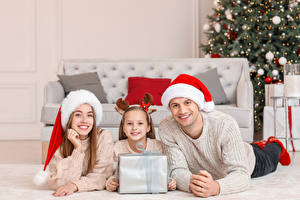 Wallpaper New year Mother Men Three 3 Little girls Winter hat Gifts Staring Family Esting child
