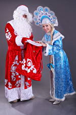 Images Christmas Two Santa Claus Smile Uniform Snow maiden young woman