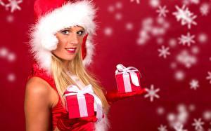 Bilder Neujahr Schneeflocken Blondine Mütze Starren Hand Handschuh Geschenke Roter Hintergrund junge frau