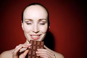 Bakgrunnsbilder Sjokolade Fingre Sjokoladeplate Farget bakgrunn Ansikt Smil Glad ung kvinne
