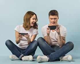 Bilder Mann Farbigen hintergrund Zwei Sitzt Smartphone Braune Haare Lacht Hand Jeans Spielt junge frau
