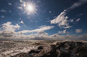 Pictures Sea Stones Sky Water splash Rays of light Sun Nature