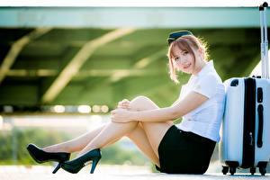 Bilder Asiaten Sitzt Unscharfer Hintergrund Bein Schöne High Heels Uniform Koffer Flugbegleiter Posiert junge frau