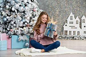 Fotos Neujahr Braune Haare Sitzend Lächeln Geschenke Kugeln Mädchens