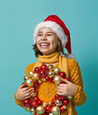 Hintergrundbilder Neujahr Farbigen hintergrund Kleine Mädchen Lächeln Mütze Kugeln Hand kind
