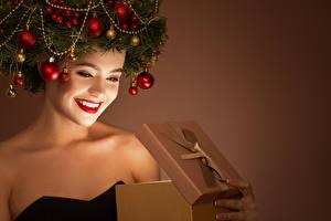 Bilder Neujahr Kreative Farbigen hintergrund Gesicht Lächeln Rote Lippen Geschenke Ast Kugeln junge frau