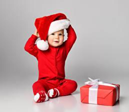 Bilder Neujahr Grauer Hintergrund Baby Uniform Mütze Geschenke Sitzend