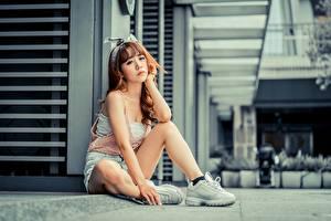 Bilder Asiaten Posiert Sitzt Sportschuhe Shorts Bein Braune Haare Unscharfer Hintergrund junge frau